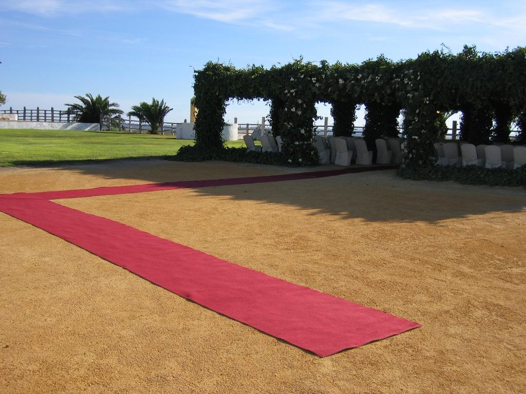 Ceremonia civil en la pérgola con alfombra roja en Dehesa Bolaños