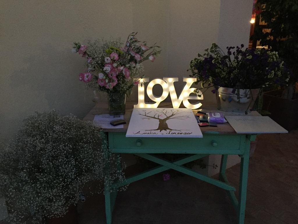 Mesa de firmas con letras iluminadas y centros de flores en Dehesa Bolaños