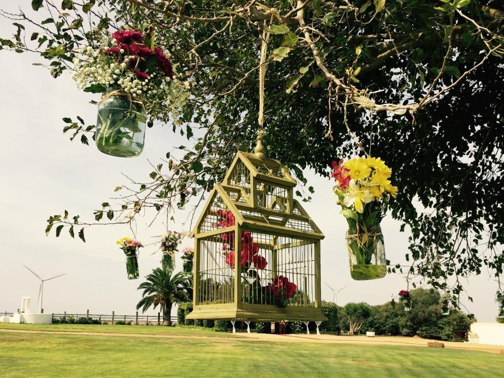 Jardines desde árbol con jaulas y tarros de flores en Dehesa Bolaños