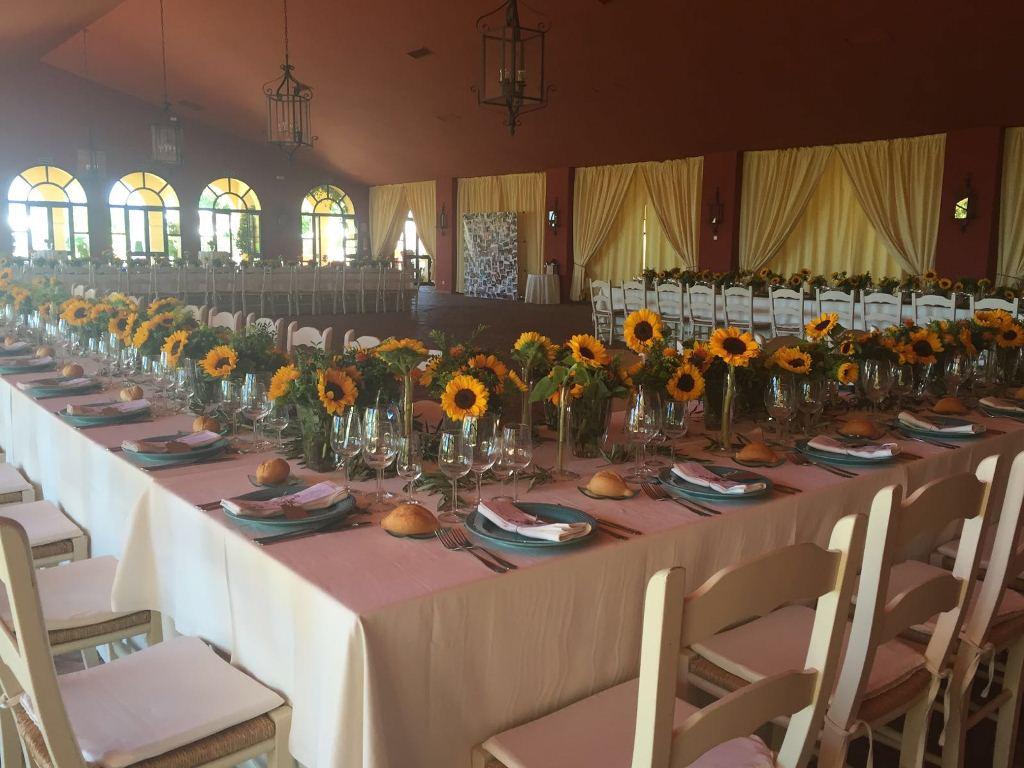 Salones con mesas imperiales y centros de girasoles para evento en Dehesa Bolaños