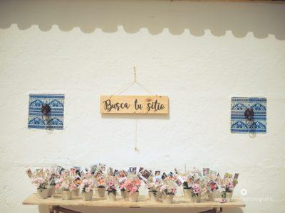 Seating plan en mesa antigua con macetas y fotos de invitados - Boda Carmen & Alexis en Dehesa Bolaños