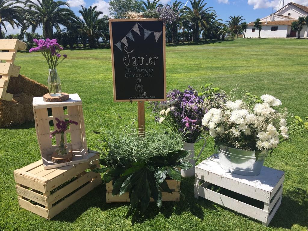 Cartel de bienvenida decorado con cajas y centros de flores - Comunión Javier en Dehesa Bolaños